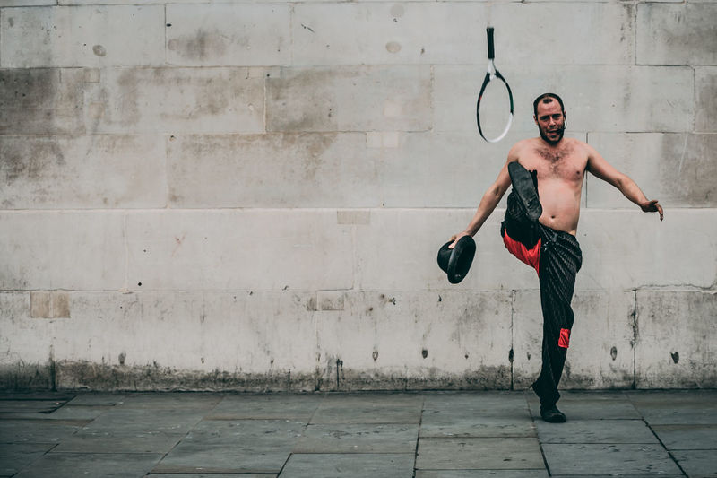 Full Length Of Shirtless Man Performing While Standing Against Wall