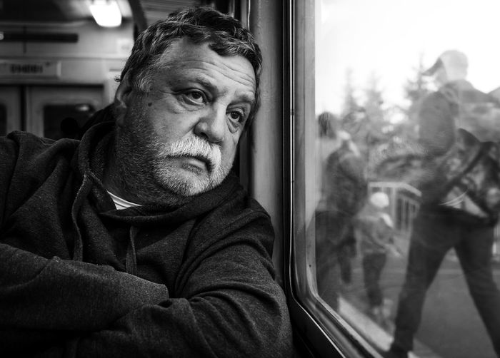 Adult Front View Glass - Material Indoors  Lifestyles Looking Looking At Camera Males  Mature Men Men One Person Portrait Public Transportation Rail Transportation Real People Train Train - Vehicle Warm Clothing Window