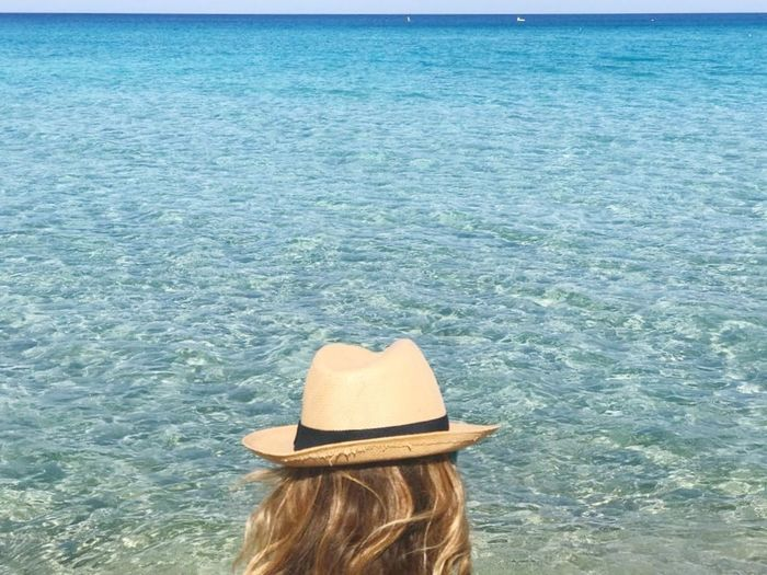Rear view of woman in hat against sea
