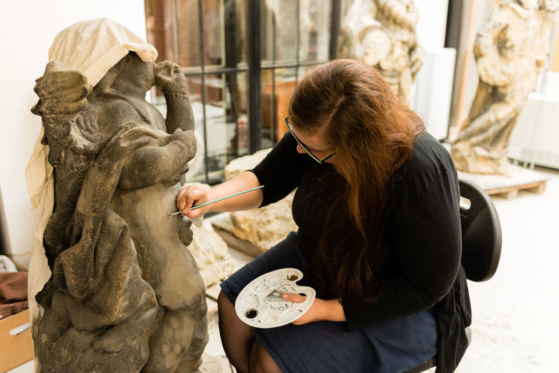 photo of a woman women restoring statue. Czech Republic Restoration Restoration Of Monuments Adult Art And Craft Casual Clothing Craft Creativity Day Hairstyle Holding Long Hair People Real People Restoration Project Sculptor Sculpture Statue Three Quarter Length Women Young Adult Young Women