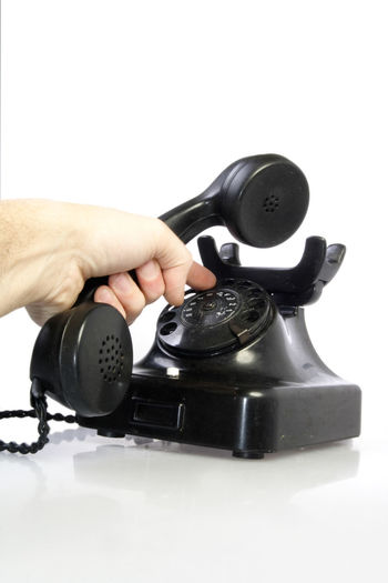 Close-up of hand using black retro telephone over white background