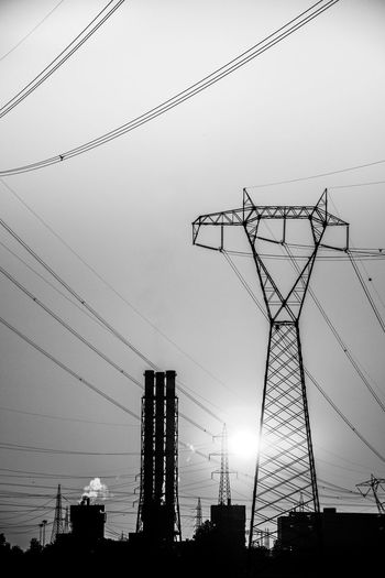 Low angle view of silhouette electricity pylon and buildings against sky