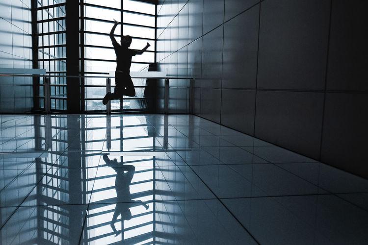 Silhouette boy jumping on tiled floor