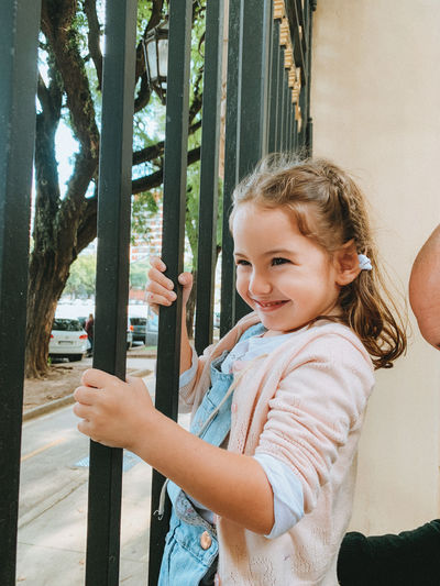 Side view portrait of smiling girl standing outdoors