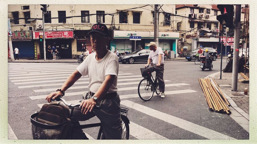 Streetphotography Transportation City Street Real People Mode Of Transportation Bicycle Architecture Land Vehicle Building Exterior People Auto Post Production Filter Men Lifestyles Day Sunlight Group Of People Built Structure City Life Transfer Print Road