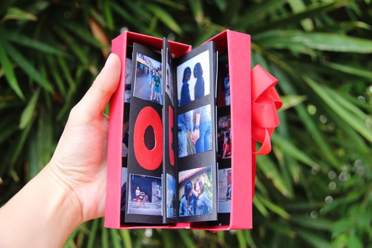 Close-up of hand holding photographs in red gift box
