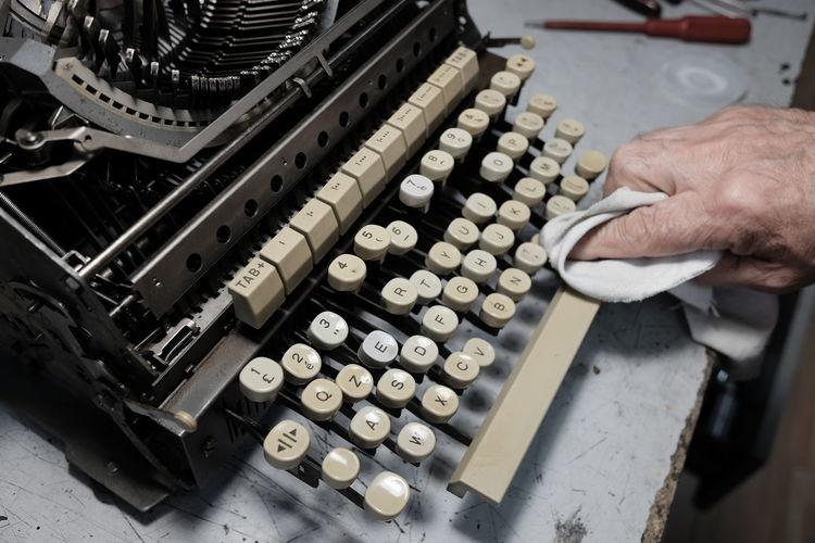 Man Cleans Typewriter Old Typewriter Obsolete Technology Obsolete Human Hand Typewriter Occupation Technician Technology Close-up Machine Part Analog Vintage Machine Typing