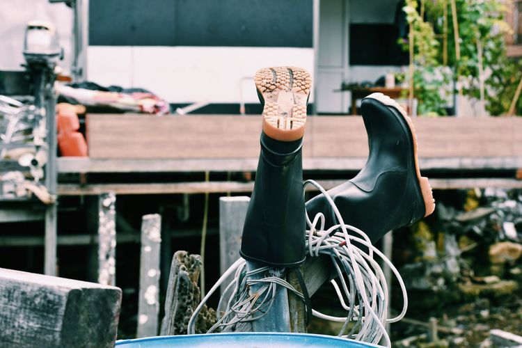 Rubber boots and cable on wooden post