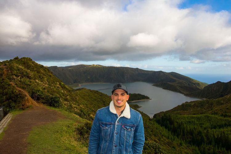 Portrait of smiling young man standing on mountain against cloudy sky
