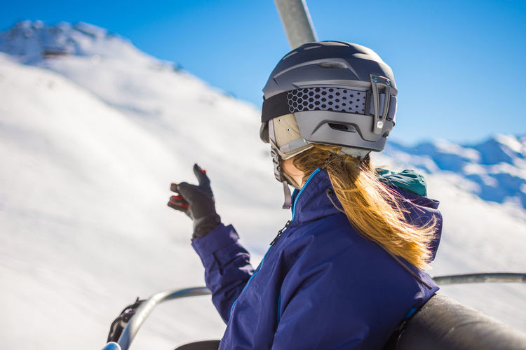 Girl / woman on vacation during winter, enjoying the snow capped French Alps. In the mountains with her snowboard, helmet and gloves in the ski lift Winter Snow Cold Temperature Warm Clothing Clothing One Person Mountain Real People Winter Sport Nature Portrait Day Headshot Sky Leisure Activity Mountain Range Technology Sport The Traveler - 2019 EyeEm Awards