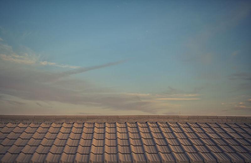 Tilt image of roof tiles against sky