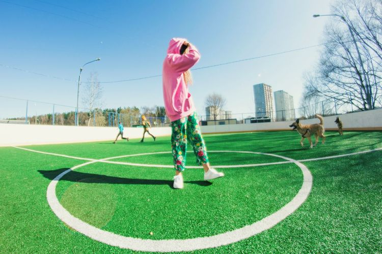 Woman Standing On Soccer Field In City Against Clear Blue Sky
