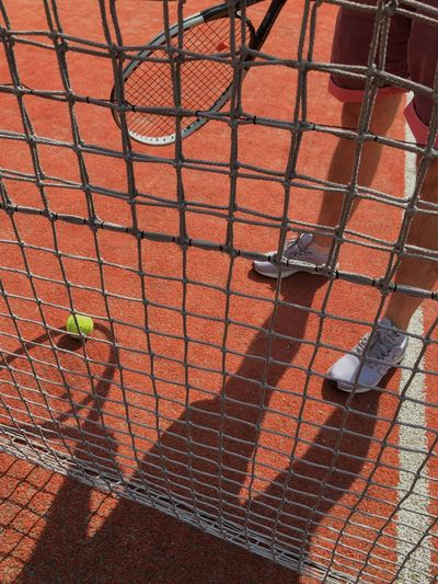 Low Section Of Player Standing By Net In Tennis Court