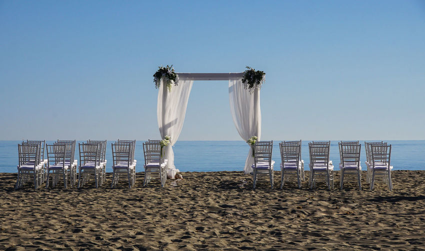 Chairs Arranged At Beach For Wedding Ceremony