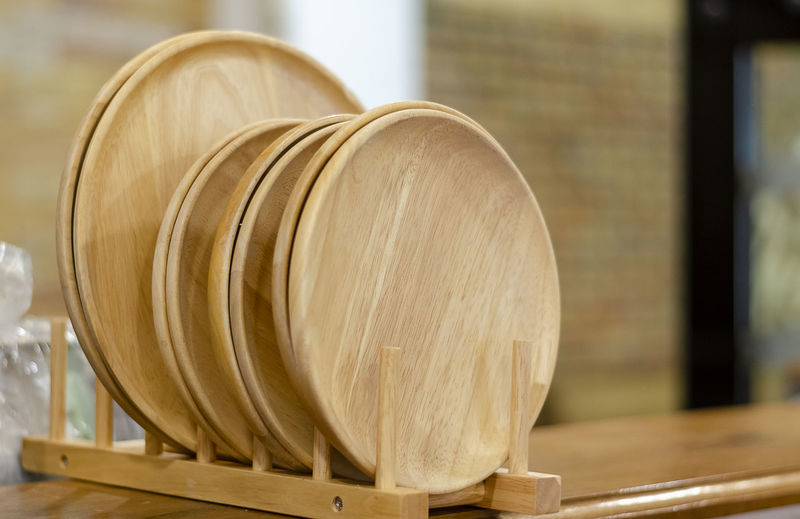 Close-up of wooden plate on the shelf