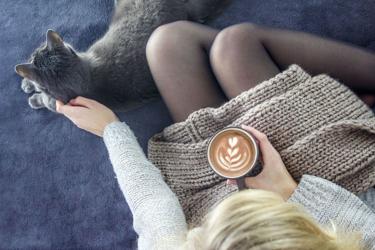 One Person Leisure Activity Real People Lifestyles Personal Perspective Human Body Part Holding Human Hand Human Leg Indoors  Close-up Adults Only Day Adult One Young Woman Only Warm Clothing Sweater Only Women One Woman Only Adults Only Coffee Cat Sofa Girl Rest