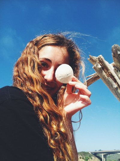 Low angle portrait of young woman holding sand dollar in front of eye