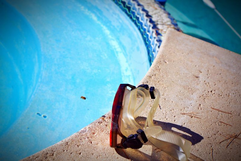 High angle view of swimming goggles at poolside