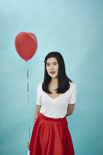 Portrait Of Woman Holding Heart Shape Balloon Against Blue Background