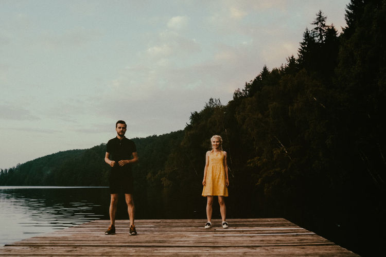Portrait of young couple standing on pier over lake against sky
