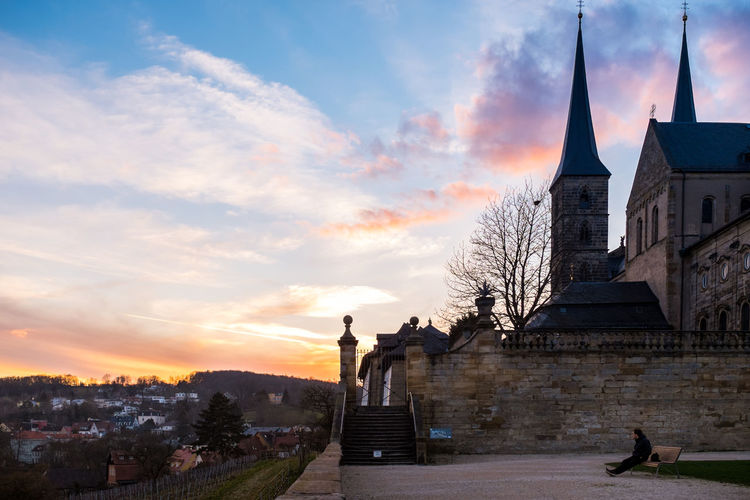 Michaelsberg abbey in town against sky during sunset