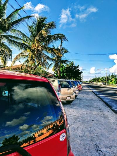 Car on road by palm trees against blue sky