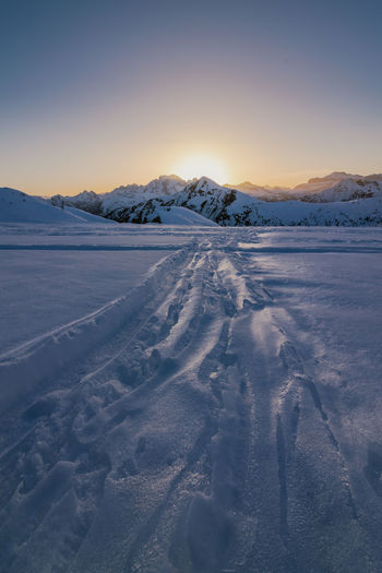 Snow covered landscape against sky during sunset