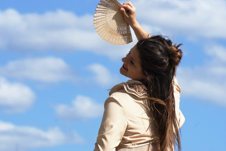 Woman with paper fan posing against blue sky