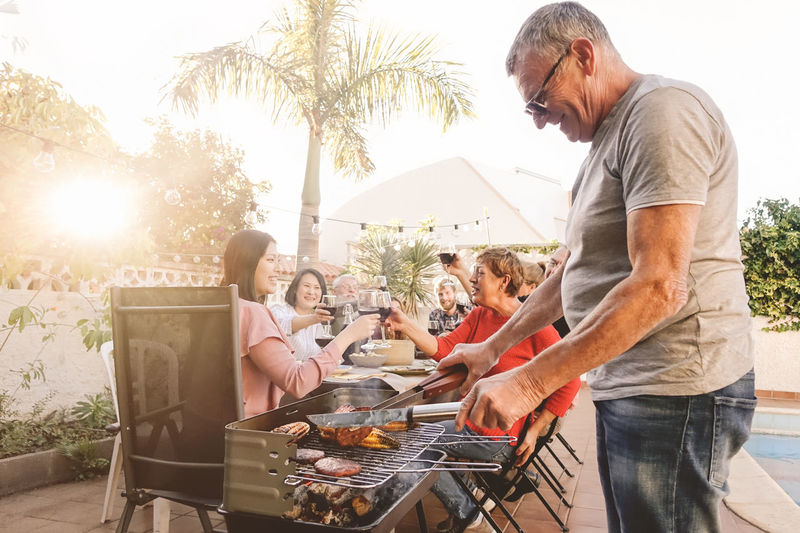 Man and woman standing on barbecue grill