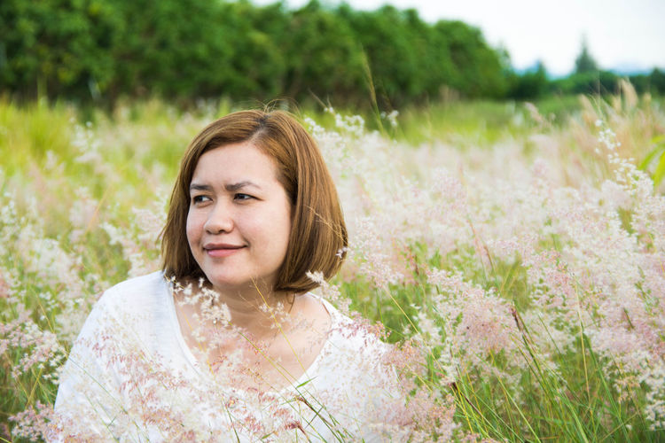 Smiling Woman Looking Away Amidst Flowers On Field