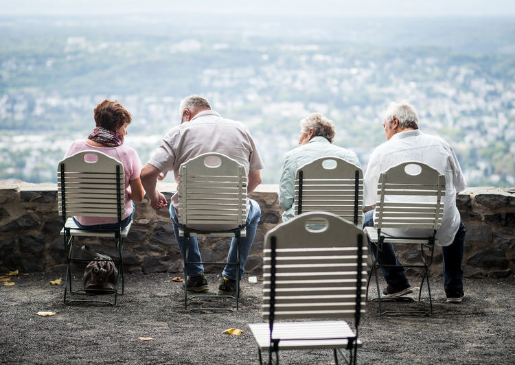 Rear View Of People Sitting On Chairs