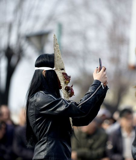 Side View Of Woman Taking Selfie While Wearing Mask At Carnival
