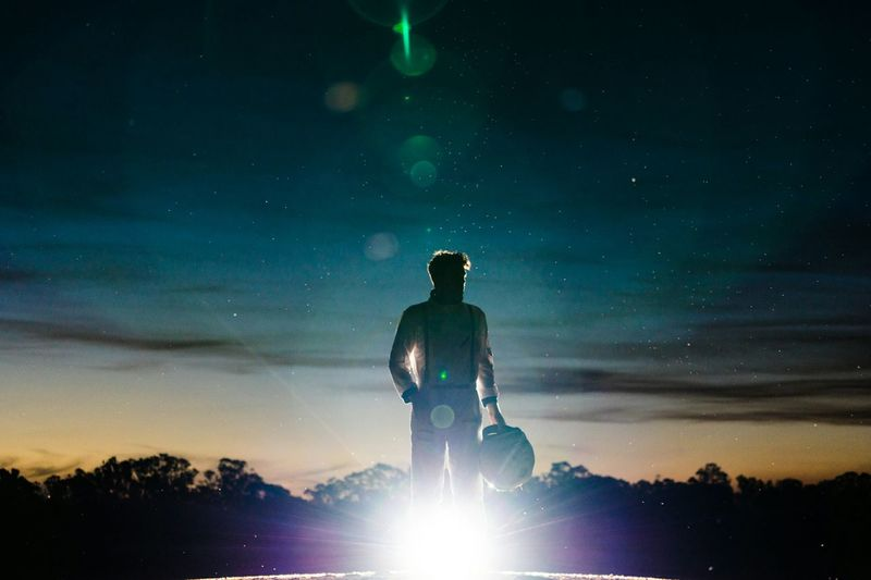 Man wearing space suit standing against sky during dusk