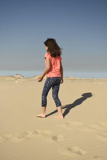 Full length of a girl on the beach against clear sky