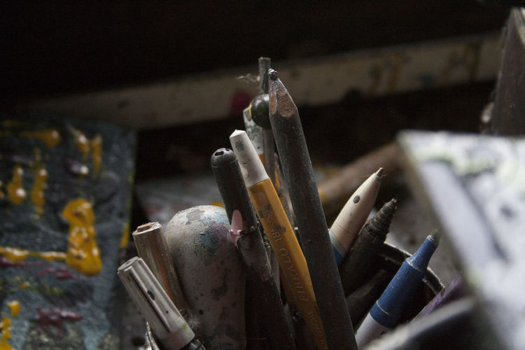 Close-up of old felt tip pens and colored pencil in desk organizer on table