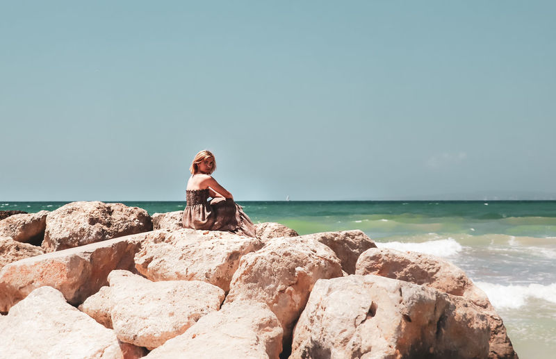 Side View Of Mid Adult Woman Sitting On Rock By Sea Against Clear Sky During Sunny Day