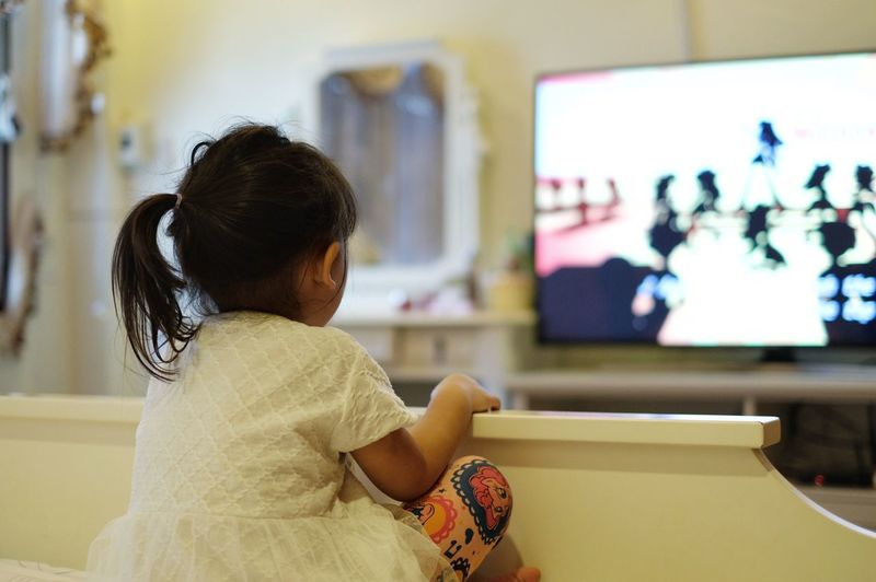 Asian little girl watching a television. Watching Tv Television One Person Indoors  Real People Sitting Women Focus On Foreground Waist Up Home Interior Technology Adult Holding Looking Leisure Activity Rear View Computer Females Lifestyles