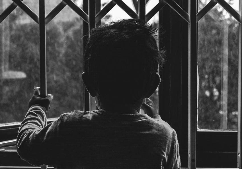 Watching the rain drop Best Of EyeEm Black And White Boy Caged Caged Freedom Childhood Close-up Day Freedom Hope Hopes And Dreams Kid Lifestyles Locked Locked Up Looking Out Looking Out Of The Window One Person Outdoors People Prison Real People Rear View Technology Welcome To Black Resist