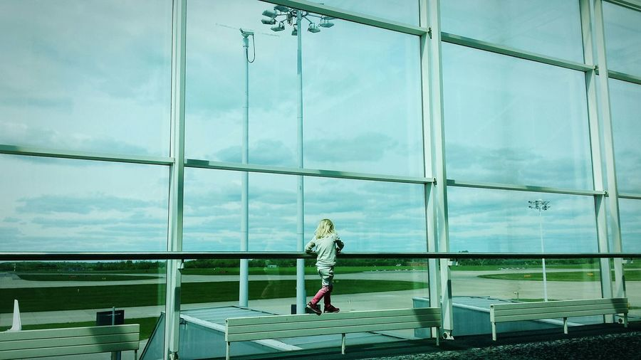 Full Length Of Girl Walking By Glass Wall In Modern Airport Lobby