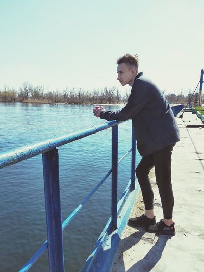 Side view of young man standing by railing against sky