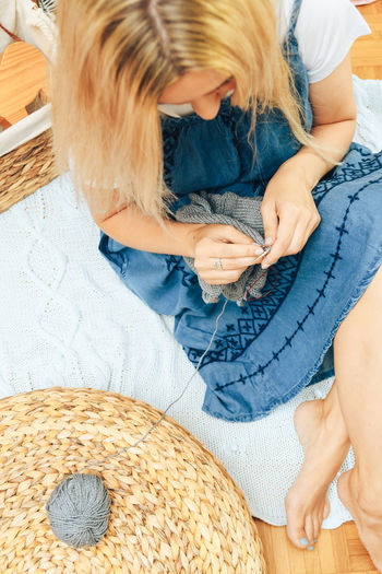 Knitting Hobby Blond Hair Hair Childhood Women One Person Child High Angle View Sitting Casual Clothing Offspring Girls Females Indoors  Adult Lifestyles Leisure Activity Real People Full Length Flooring Hairstyle