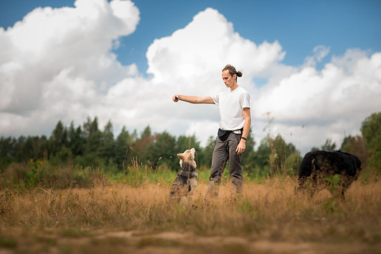 Man playing with dogs while standing on grassy land against cloudy sky