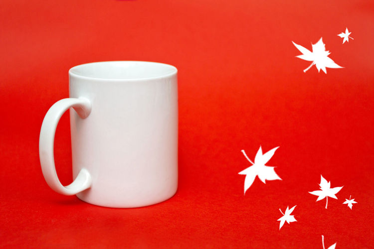 Close-Up Of Mug With Christmas Decoration On Red Background