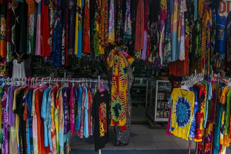 Multi colored clothes hanging for sale at market stall