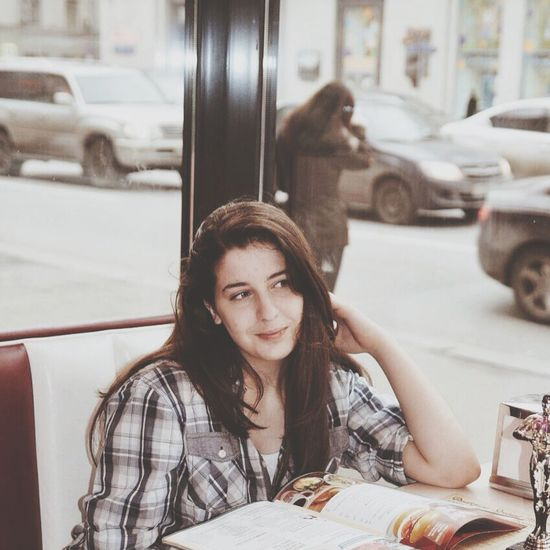 Young woman looking away while sitting at restaurant