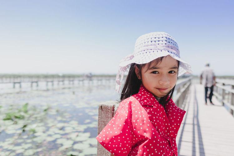 Portrait of cute girl wearing hat against water