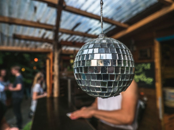 Disco ball in a club in Berlin Berlin Music Celebration Christmas Decoration Christmas Ornament Close-up Day Disco Ball Focus On Foreground Hanging Illuminated Incidental People Indoors  Men Nightclub One Person People Real People Women