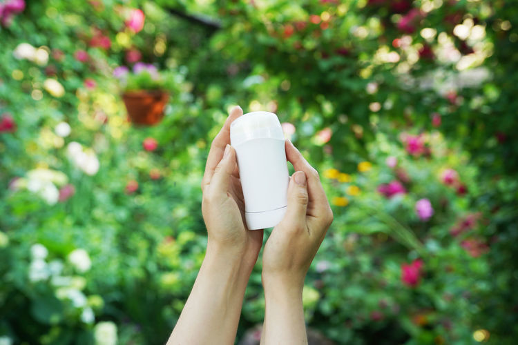 Hands holding natural deodorant on green flowers background. zero waste concept