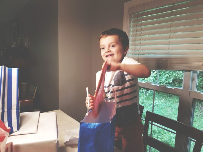 Cute boy looking away while holding bag at home