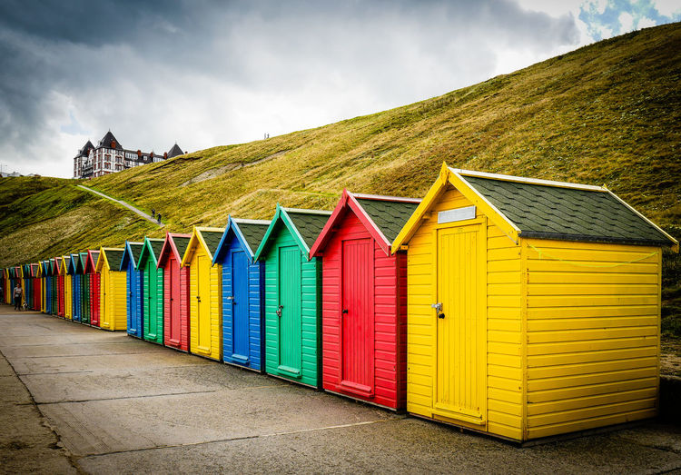 Colorful Beach Huts In Row By Hill